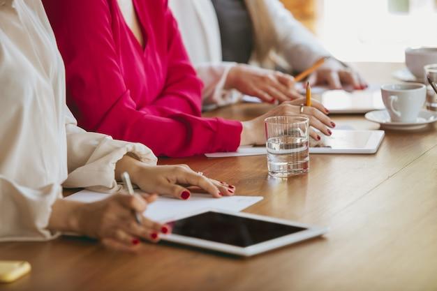 Закройте вверх женские руки написание заметок во время творческой встречи, обсуждения, проекта, работающего в офисе. понятие финансов, бизнеса, женской силы, включения, разнообразия. с помощью планшетов, ноутбуков, смартфонов.