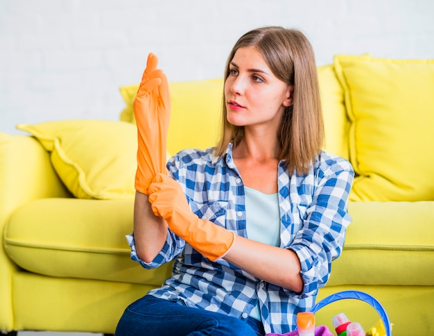 Close-up of female janitor sitting in front of yellow sofa wearing an orange gloves