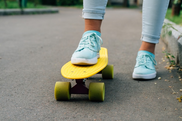 Close-up of female legs in blue jeans and sneakers standing on a yellow skateboard
