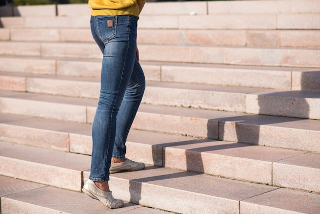 Close up of female legs climbing the steps up.