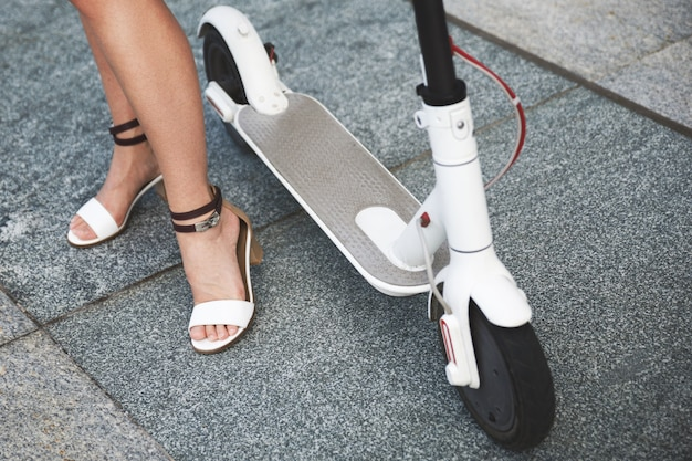 Close-up of female legs on the electric scooter