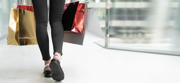 Close-up of female legs walking in the mall. colored shopping bags. baner place for text. copy space
