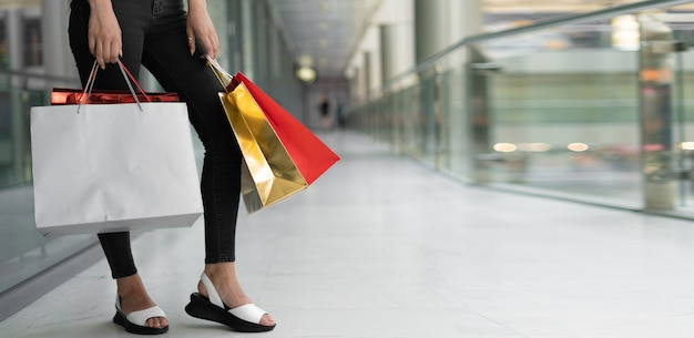 Close up of female legs with several colored packages in hands. shopping mall concept. baner place for text.