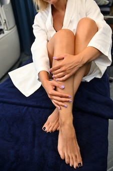 Close-up of female legs with smooth skin on a blue towel at the spa during laser treatment. hair removal concept