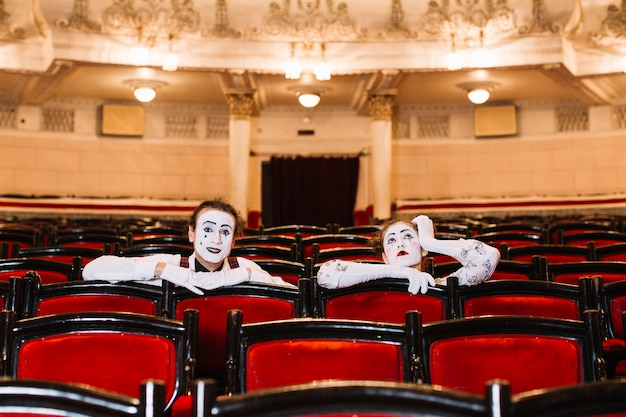 Close-up of female and male mime sitting on arm chair in the auditorium