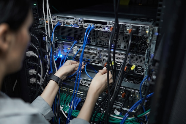 Close up of female network technician connecting cables in server cabinet while setting up supercomputer at data center, copy space