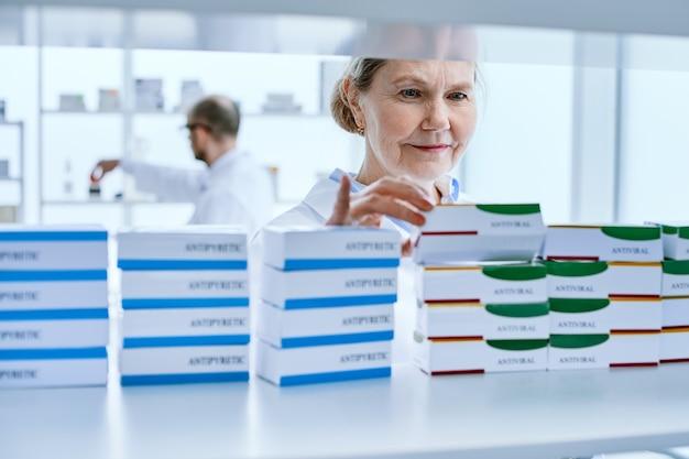 Крупный план. фармацевт-женщина, стоящая перед полкой с лекарствами. фото с копировальным пространством.