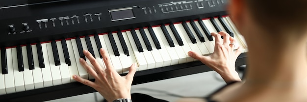 Close-up of female playing on electrical piano instrument. black and white key. sheet music with song. young woman exercise at home. spare time and hobby concept