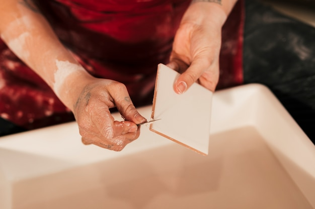 Close-up of female potter carving the white tiles with tools