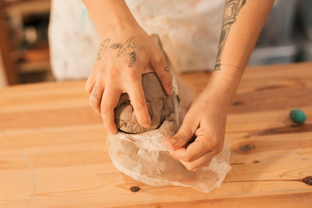 Close-up of female potter's hand removing the clay from plastic paper on wooden table