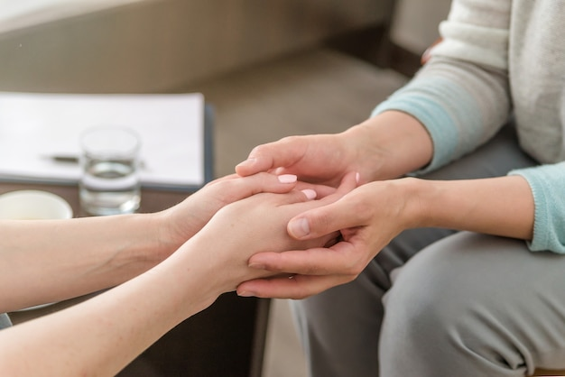 Close up of female psychologist holding hands of senior women during therapy session.