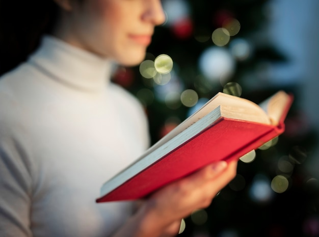Close-up female reading christmas stories book