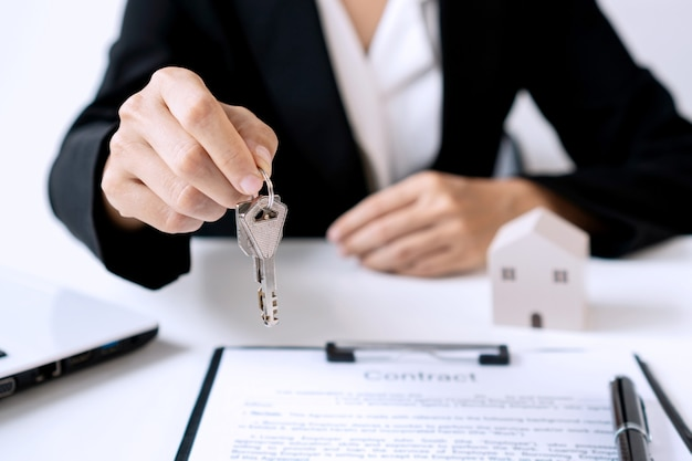Close up of female real estate agent giving house key to her client after signing contract