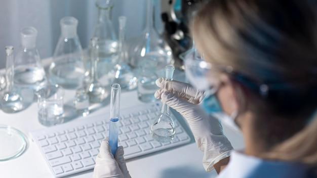 ガラス製品を保持しているクローズアップの女性研究者