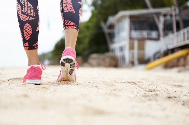 Close up of female runner wearing pink sneakers and leggings walking or running on beach sand while exercising outdoors against blurred bungalow. view from the back.