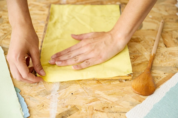 Close-up of a female's hand covering paper pulp with yellow cloth