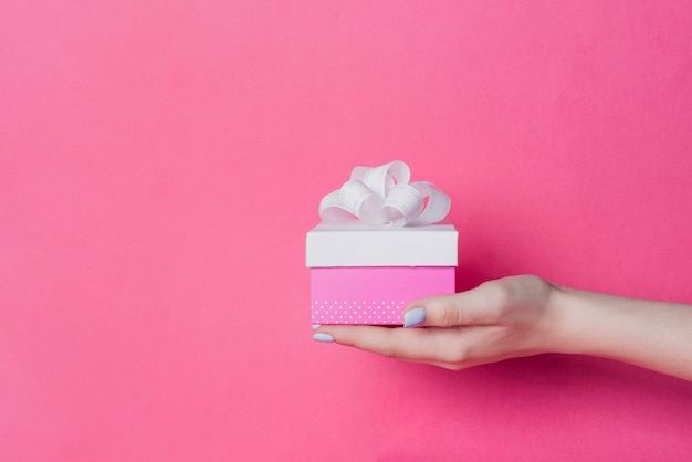 Close-up of female's hand holding box with white ribbon bow on pink background