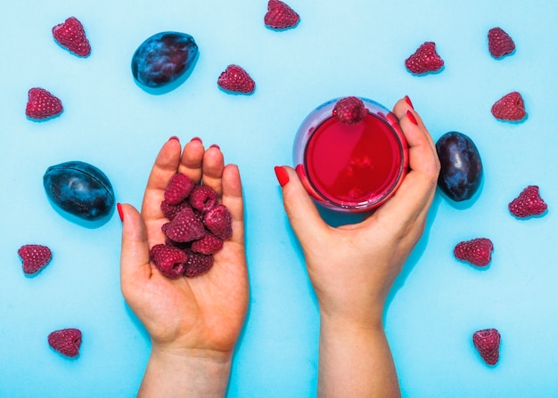 Close-up of a female's hand holding juice of plums and raspberries on blue background
