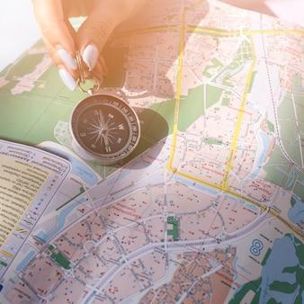 Primo piano della mano della femmina che tiene bussola di navigazione sulla mappa