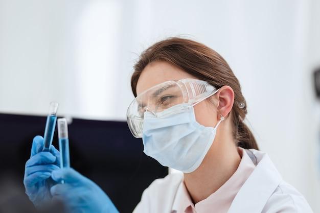 閉じる。試験管内の液体を見ている女性の科学者。科学と健康。