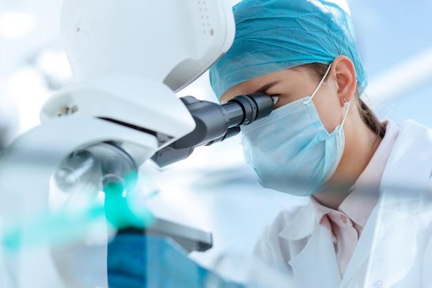 Закройте вверх. женщина-ученый, внимательно глядя в микроскоп. наука и охрана здоровья.