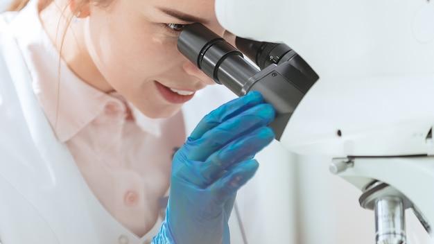 閉じる。顕微鏡を通して見ている女性の科学者。科学と健康。