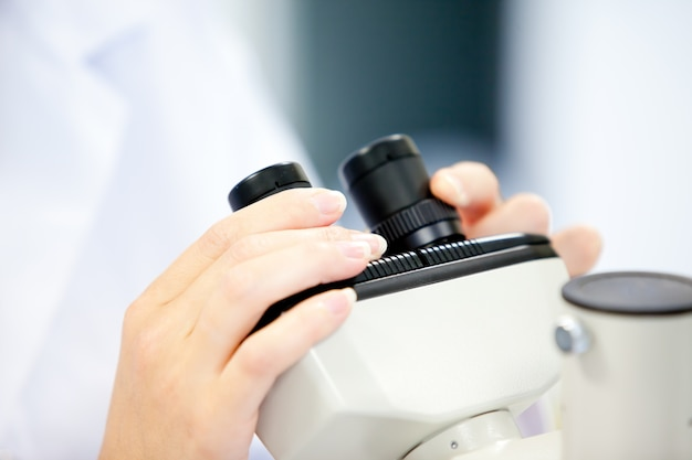 Close-up of a female scientist looking through a microscope