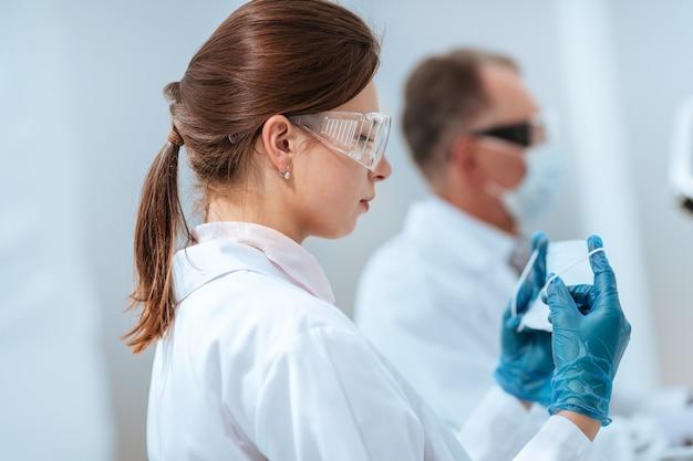 閉じる。研究室で保護マスクを着用している女性科学者。