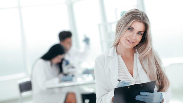 확대. 클립 보드에 메모를 복용하는 여성 과학자. 복사 공간 사진