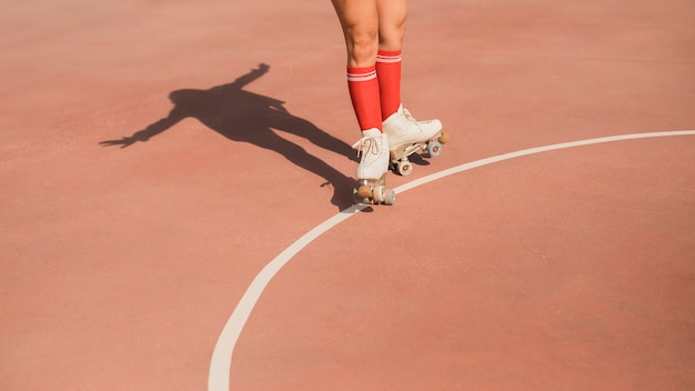 Close-up of female skater's shadow on court