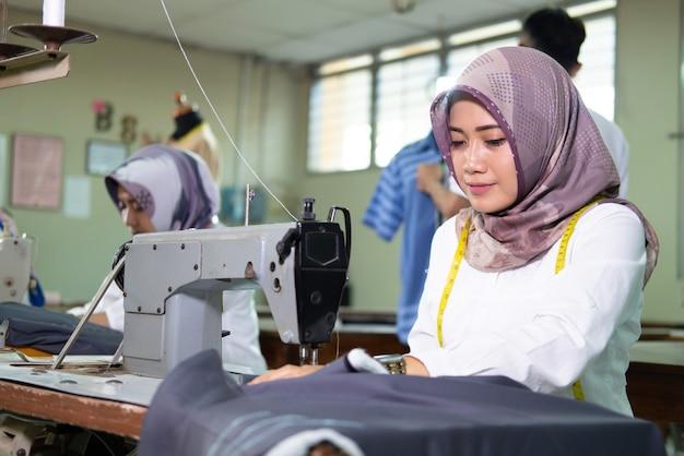 作業中にミシンを使用してヒジャーブで女性の仕立て屋をクローズアップ