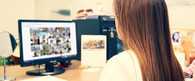 Учительница крупным планом использует портативный компьютер для обучения студентов онлайн.