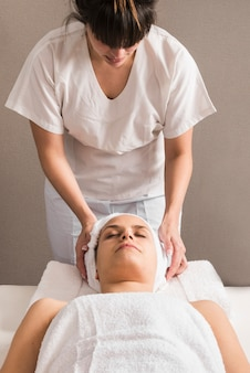 Close-up of a female therapist wrapping towel on woman's head