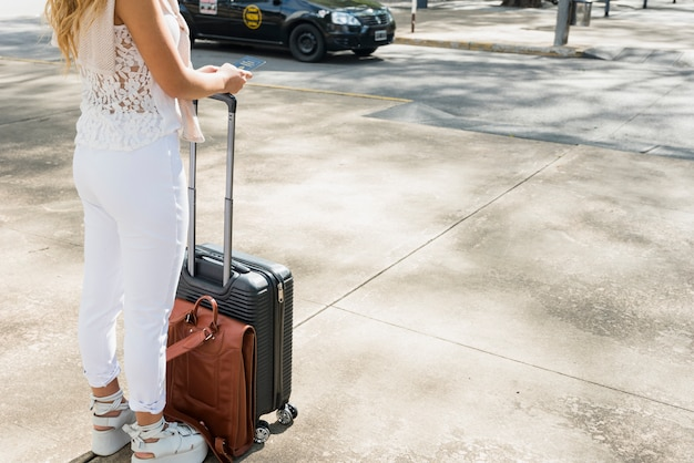 Close-up of female tourist standing on road holding luggage travel bag and passport
