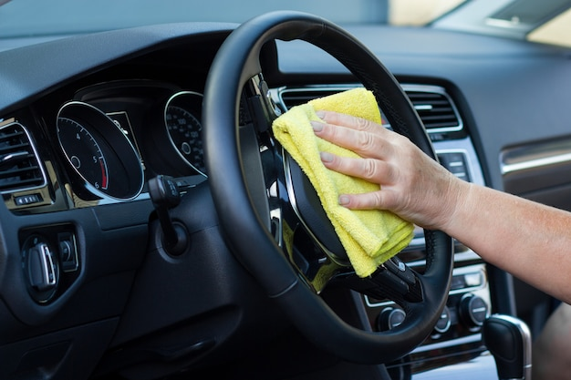 Close-up of a female worker cleaning car steering wheel with a soft cloth.