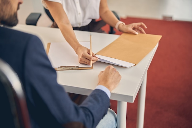 Close up of female worker pulling out sheet of paper from envelope while sitting across the table from man