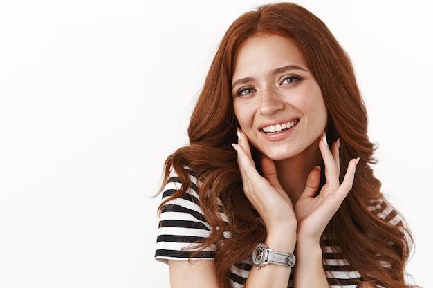 주근깨가 있는 여성스럽고 현대적인 빨간 머리 소녀, 완벽한 깨끗한 피부, 여드름과 흠집을 없애고 턱선을 만지고 머리를 기울이고 어리석게 웃고 서 있는 흰색 벽이 귀엽습니다.