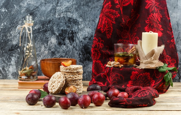 Close-up fermented drink and candle on red scarf with wafers,jug vase,a bowl,plums and red scarf on wooden board and dark grey marble background. horizontal free space for your text
