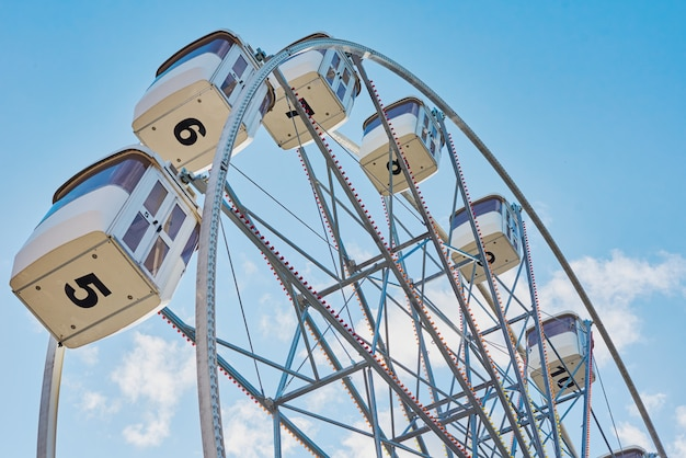 Close up of ferris wheel against blue cloudy sky