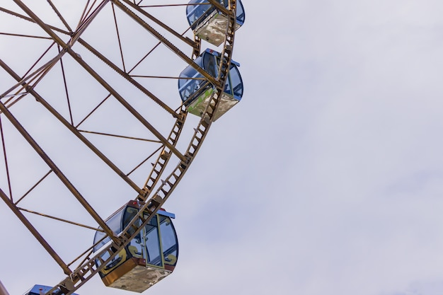 Close up of ferris wheel cabins on cloudy sky background.