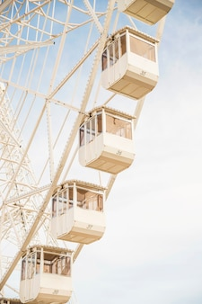 Close-up of ferris wheel white cabins against blue sky
