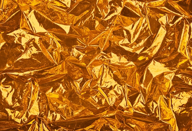 Close up festive abstract background of golden orange crumpled glossy metallic plastic foil