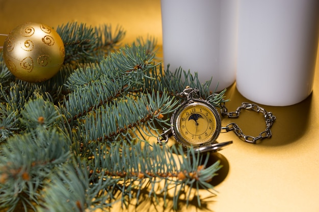 白い柱のキャンドルと黄色の背景にシングルゴールドのクリスマスボールで飾られた常緑の枝に囲まれたアンティーク懐中時計のお祝いの静物をクローズアップ