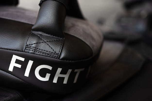 Close up of fight word on black boxing and kicking practice pad.