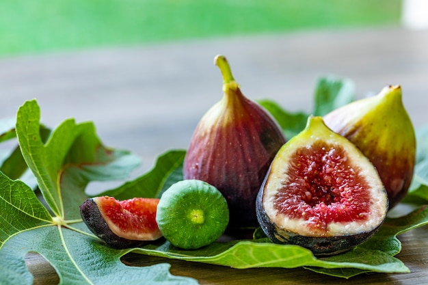 Close up of figs on top of green leaves on rustic wooden table