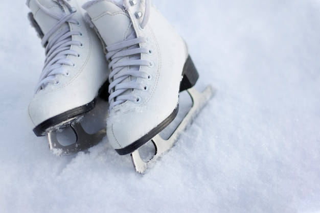 Close-up of figure skates on an ice. ice skating outdoor activities with the family in winter.