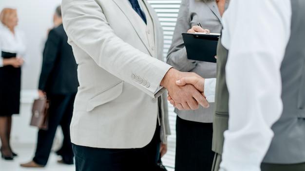 Крупным планом финансовые партнеры, пожимая руки в офисе