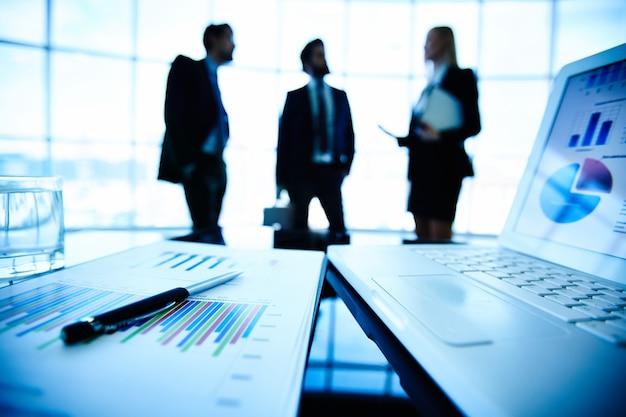 Primo piano di una relazione finanziaria con sfondo uomini d'affari
