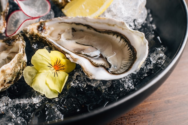 Close up fine de claire oyster and lemon served in black bowl with ice on wooden table.