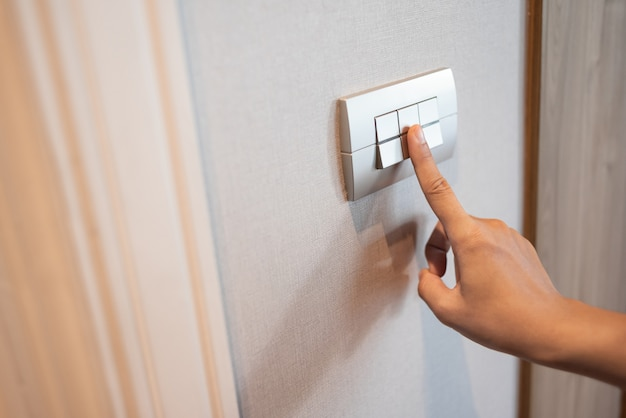Close up of finger is turning on or off in light switch.